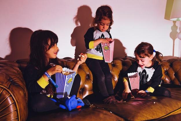Małe dziewczynki z popcornem na kanapie Darmowe Zdjęcia