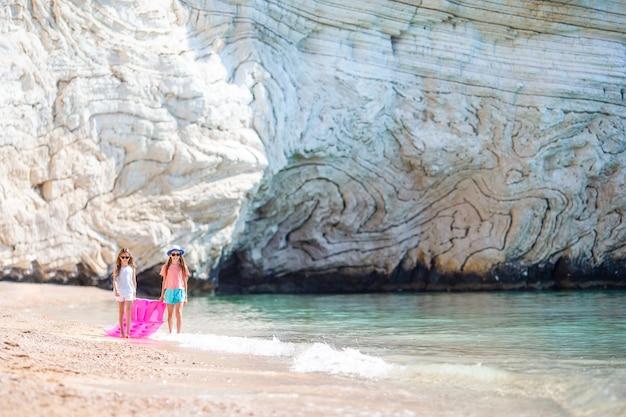 Małe dziewczynki zabawy na tropikalnej plaży podczas letnich wakacji, grając razem Premium Zdjęcia