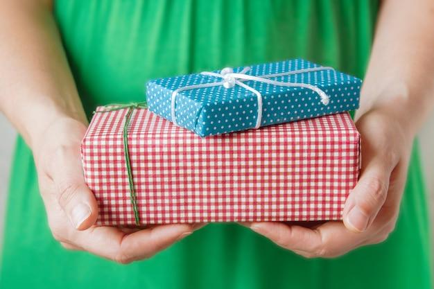 Małe prezenty w rękach kobiety. koncepcja bożego narodzenia. Premium Zdjęcia