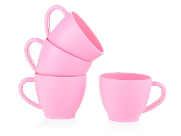 Małe Różowe Kubki Dla Dzieci Stoją Jeden Na Drugim Na Białym Tle. Premium Zdjęcia