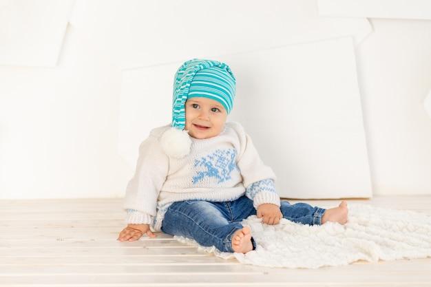 Małe Szczęśliwe Dziecko W Wieku Sześciu Miesięcy W Ciepłej Kurtce Z Dzianiny I Czapce Siedzi W Domu Na Dywanie W Jasnym Pokoju Premium Zdjęcia