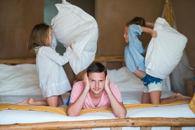 Małe urocze dziewczynki walczące z poduszkami w pobliżu ojca Premium Zdjęcia