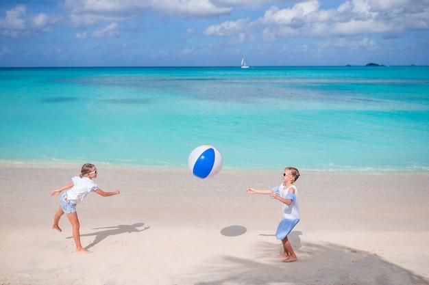 Małe urocze dziewczyny bawić się z piłką na plaży Premium Zdjęcia