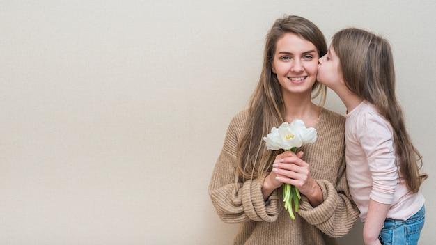 Małej Dziewczynki Całowania Matka Z Tulipanami Na Policzku Premium Zdjęcia