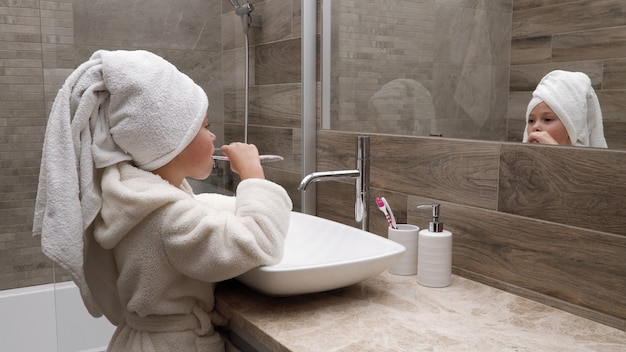 Małej dziewczynki cleaning zęby w łazience przeciw lustrze Premium Zdjęcia