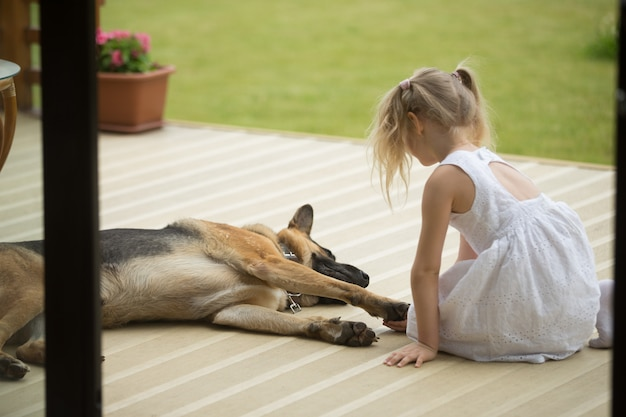 Małej dziewczynki mienia psów łapa siedzi blisko zwierzęcia domowego na ganeczku Darmowe Zdjęcia