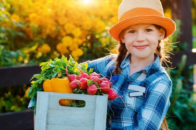 Małej dziewczynki mienia pudełko świezi organicznie warzywa Premium Zdjęcia