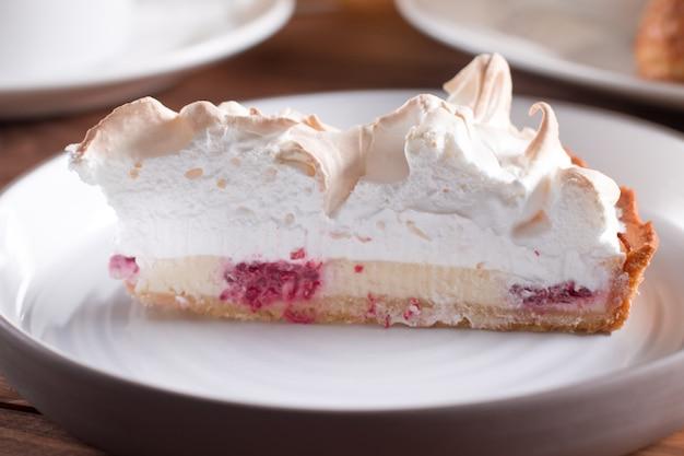 Malinowy tort z białą uwielbianą bezą na drewnianym stole Premium Zdjęcia