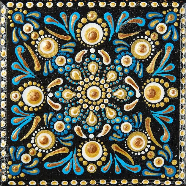 Malowanie Kropek Mandali Na Płytkach Drewnianych. Piękna Mandala Ręcznie Malowana Kolorowymi Kropkami Na Czarnym Drewnie. Premium Zdjęcia