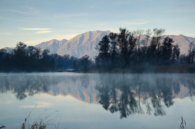 Malownicze Jezioro Z Odbiciem Gór I Drzew Pod Błękitnym Niebem Darmowe Zdjęcia