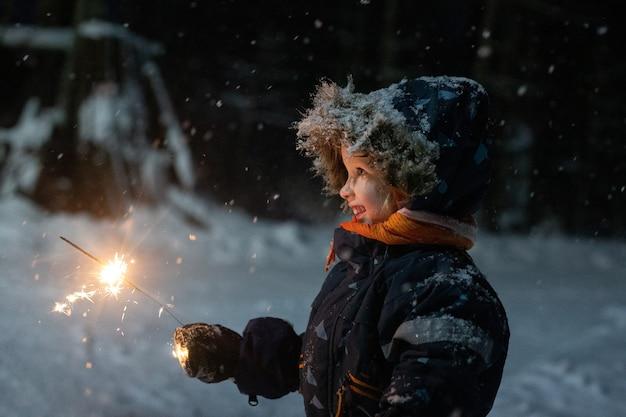 Maluch Dziewczyna W Zimowe Ubrania Spaceru Na Zewnątrz I Trzymając W Ręku Brylant. Jest Ciemno I śnieżnie, Dziewczynka Radośnie Się Uśmiecha. Magiczny Nastrój Zimowych Wakacji Premium Zdjęcia