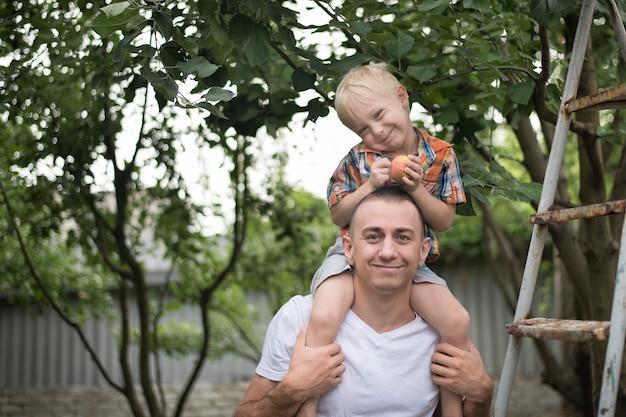 Mały blond chłopiec z jabłkiem w rękach na ramionach ojca. Premium Zdjęcia