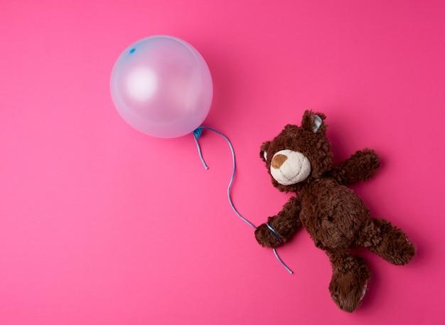 Mały Brązowy Miś Trzyma Błękitnego Napompowanego Balon Premium Zdjęcia