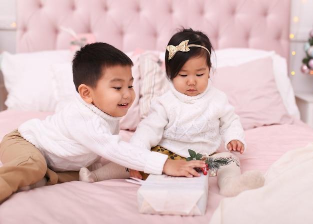 Mały Chłopiec Azjatyckich Dzieci I Kobieta W Sweterkach Otwierają Się I Bawią, Siedząc Na łóżku W Domu Premium Zdjęcia