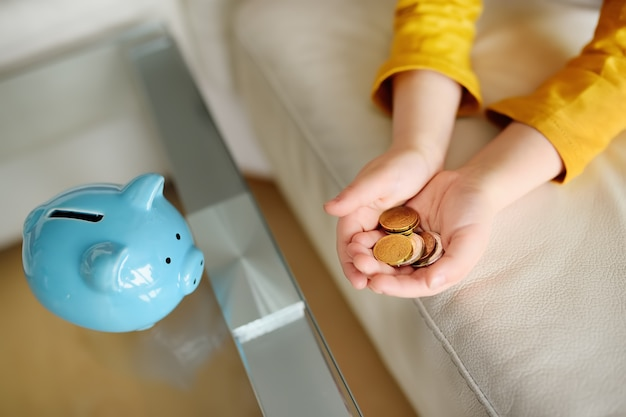 Mały chłopiec bawi się monetami i marzy o tym, co może kupić. Premium Zdjęcia