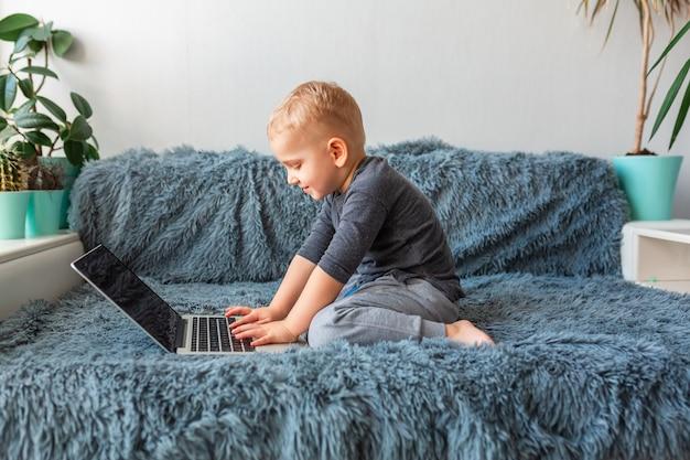 Mały Chłopiec Bawić Się Na Laptopie Na Kanapie W Domu. E-learning, Nauka Na Odległość, Koncepcja Komunikacji Na Odległość Premium Zdjęcia