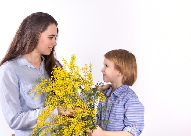 Mały chłopiec daje matce wiosenny bukiet żółtej mimozy. gratulacje 8 marca, dzień matki. Premium Zdjęcia