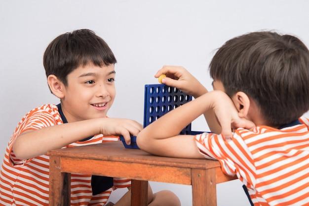 Mały Chłopiec Grający W Connect Four Game Soft Focus W Kontakcie Wzrokowym Premium Zdjęcia