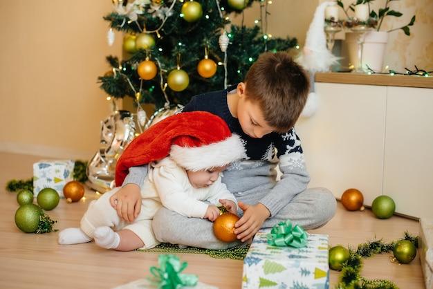 Mały Chłopiec I Jego Brat Bawią Się Prezentami Pod świąteczną Choinką Premium Zdjęcia