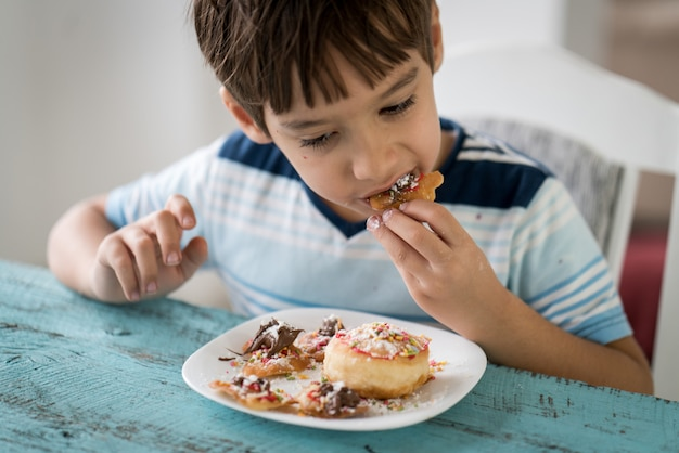Mały Chłopiec Jedzenie Pyszne Pączki Premium Zdjęcia