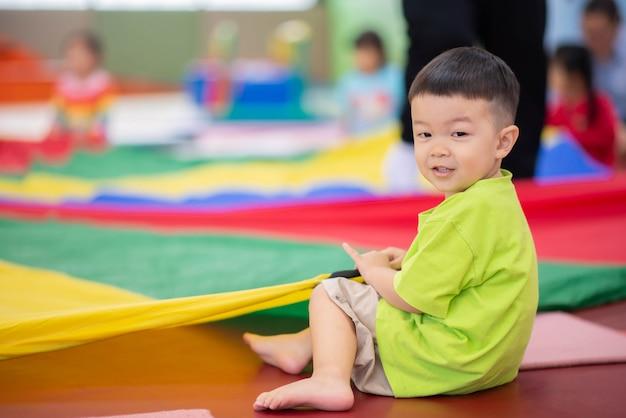 Mały chłopiec maluch, poćwiczyć w sali gimnastycznej ćwiczenia Premium Zdjęcia