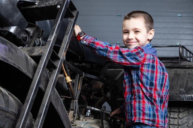 Mały Chłopiec, Młody Mechanik Samochodowy Wesoło Marzy, że Jedzie Szybko Na Motocyklu W Garażu Stacji Paliw. Dziecko Uśmiecha Się I Stoi W Pobliżu Na Starym Atv Premium Zdjęcia