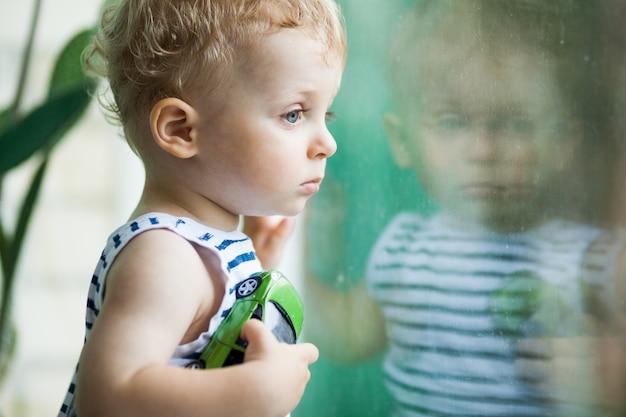 Mały chłopiec ogląda deszcz przez okno Premium Zdjęcia