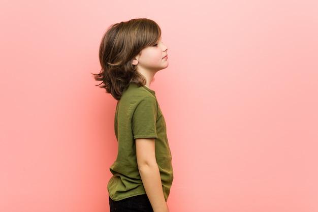 Mały chłopiec patrzy w lewo, poza bokiem. Premium Zdjęcia