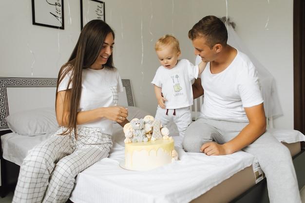 Mały chłopiec raduje się z urodzinowego tortu przedstawionego przez rodziców Darmowe Zdjęcia