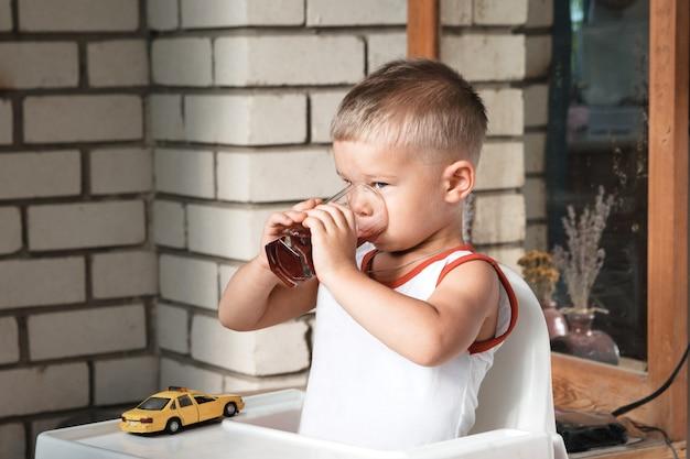 Mały chłopiec siedzi przy stoliku na werandzie i pije z dużego szklanego kubka. Premium Zdjęcia