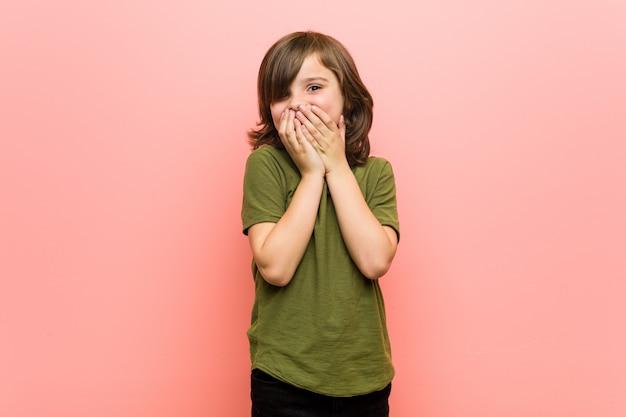 Mały chłopiec śmieje się z czegoś, zasłaniając usta dłońmi. Premium Zdjęcia