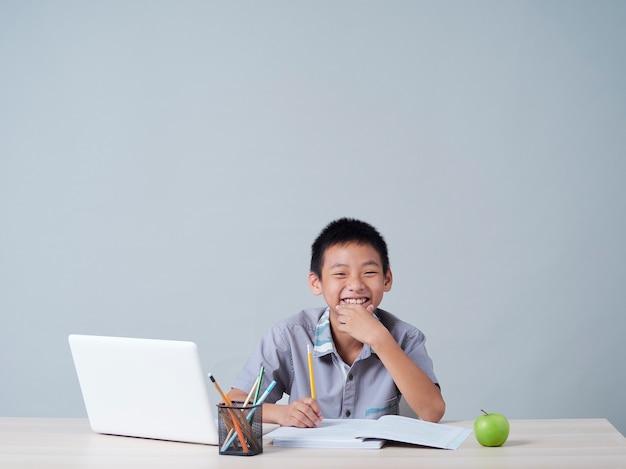 Mały Chłopiec Studiuje Online Z Laptopem. Kształcenie Na Odległość Podczas Pandemii Covid-19 Premium Zdjęcia