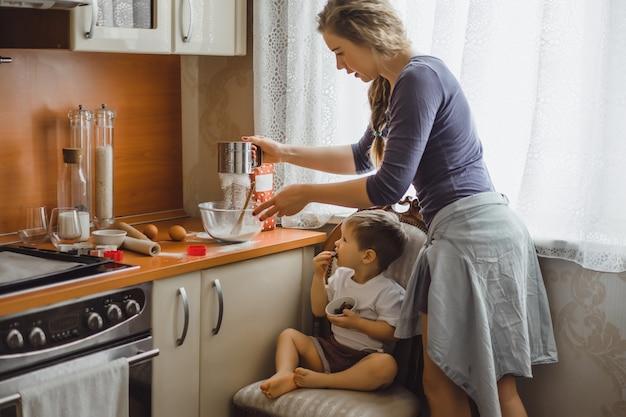 Mały chłopiec w kuchni pomaga mamie gotować. dziecko jest zaangażowane w gotowanie. Darmowe Zdjęcia