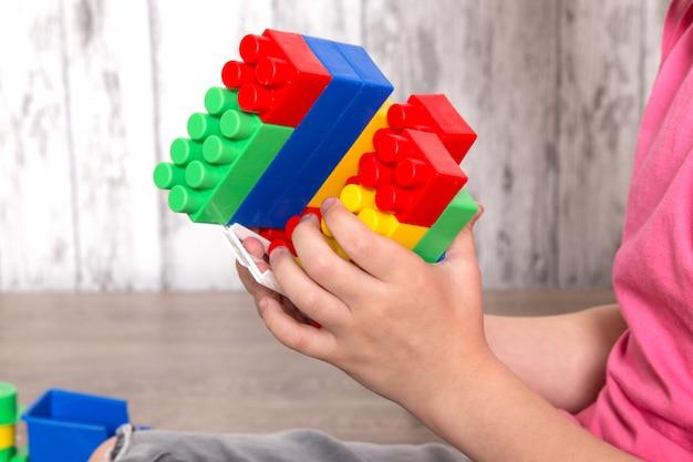 Mały Chłopiec W Różowej Koszulce I Szarych Dżinsach Bawi Się Zabawkami Darmowe Zdjęcia