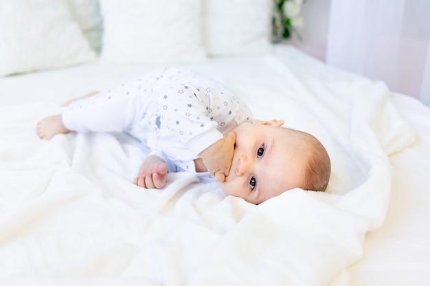 Mały Chłopiec W Wieku 6 Miesięcy Leży W Piżamie Na Białym łóżku I Ssie Palce Premium Zdjęcia