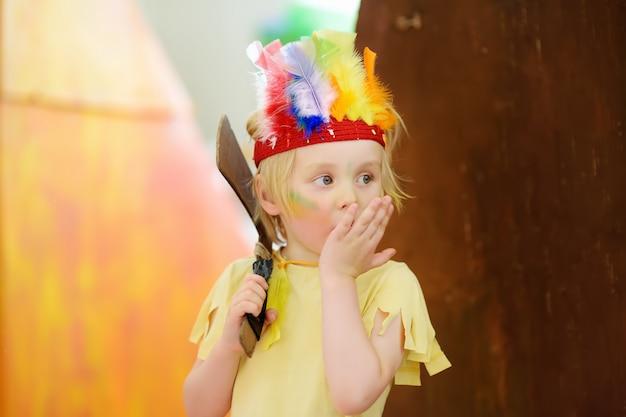 Mały Chłopiec Zaangażowany W Performance Teatru Dziecięcego Studio W Roli Indian Amerykańskich. Premium Zdjęcia