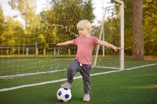 Mały chłopiec zabawy gra w piłkę nożną / mecz piłki nożnej w letni dzień. Premium Zdjęcia