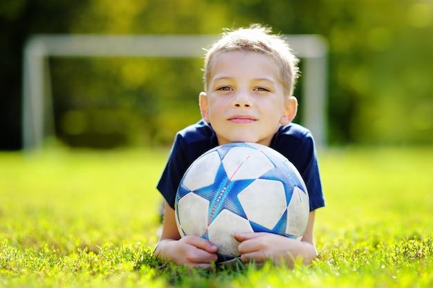 Mały chłopiec zabawy gra w piłkę nożną w słoneczny letni dzień Premium Zdjęcia