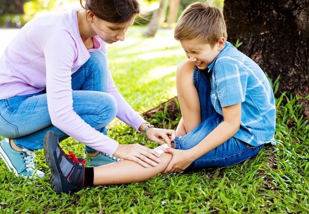 Mały chłopiec zdrapał nogę podczas gry Premium Zdjęcia