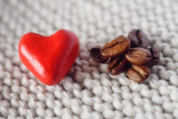 Mały czerwony serce na trykotowym tle obok kawowych adra Premium Zdjęcia