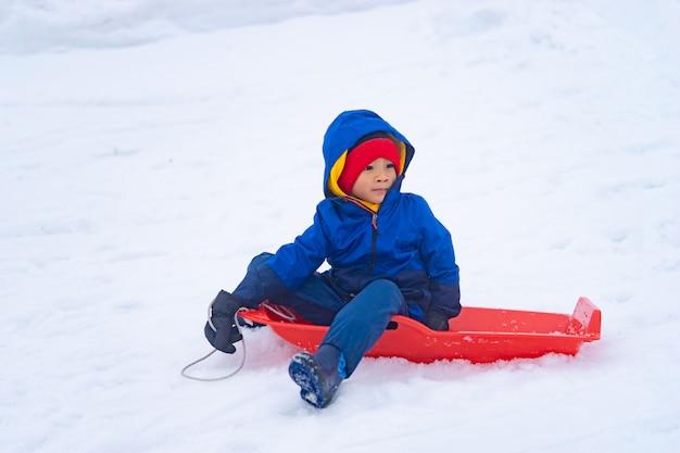 Mały japoński chłopiec zjeżdża po sankach w ośrodku narciarskim gala yuzawa Premium Zdjęcia