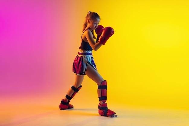Mały Kaukaski Kobieta Kick Bokser Szkolenia Na Gradientowym Tle W Neonowym świetle, Aktywne I Wyraziste Darmowe Zdjęcia