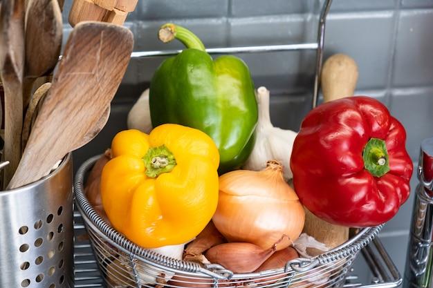 Mały Kosz W Kuchni Obok Naczyń Z Czosnkiem, Cebulą, Szalotką I Czerwoną żółtą I Zieloną Papryką Premium Zdjęcia