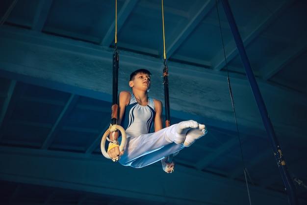 Mały Mężczyzna Gimnastyczka Trening Na Siłowni, Elastyczny I Aktywny. Kaukaski Sprawny Chłopiec, Sportowiec W Białej Odzieży Sportowej ćwiczący W ćwiczeniach Równowagi Na Pierścieniach. Ruch, Akcja, Ruch, Koncepcja Dynamiczna. Darmowe Zdjęcia