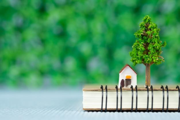 Mały model domu i małe drzewo z notebookiem Premium Zdjęcia