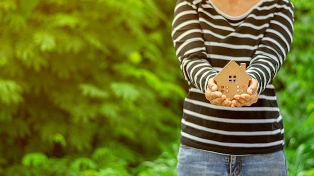 Mały model domu w ręce kobiety. - kup koncepcję domu i nieruchomości. Premium Zdjęcia