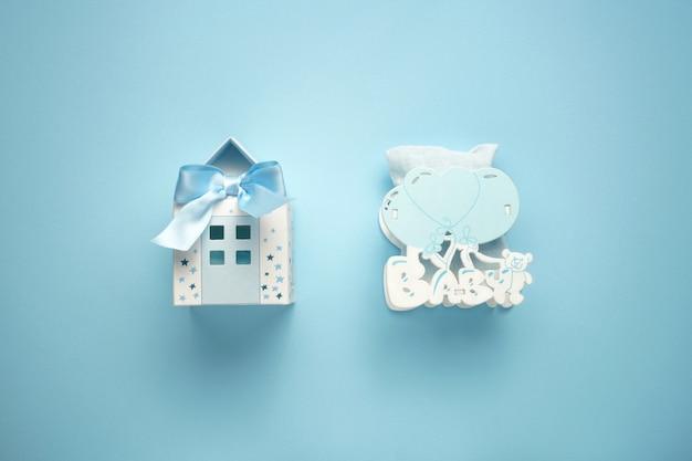 Mały papierowy niebieski dom jako kojec i dziecko drewniana zabawka z balonami na niebieskim tle Premium Zdjęcia