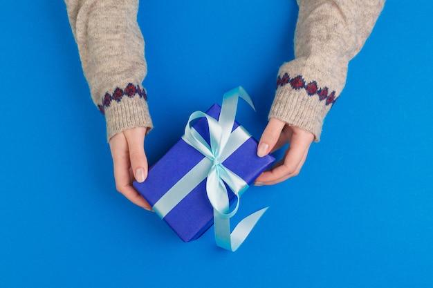 Mały prezenta pudełko w kobiet rękach na błękitnym tle, widok od above Premium Zdjęcia