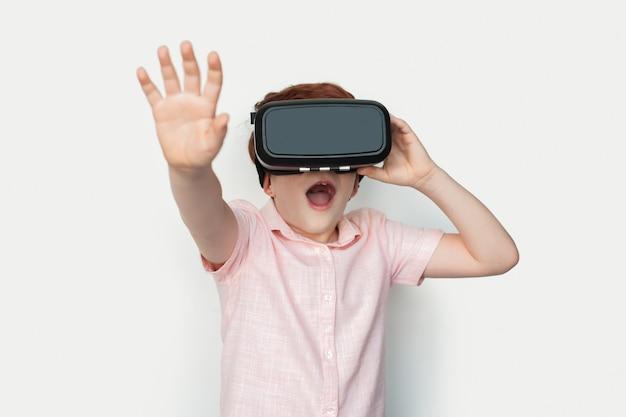 Mały Rudy Chłopiec Kaukaski W Zestawie Słuchawkowym Wirtualnej Rzeczywistości Dotyka Czegoś Na Białej ścianie Studia Premium Zdjęcia