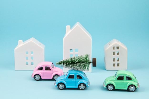 Mały samochodzik przewożący choinki nad dachem. sezonowe wakacje, karta z pozdrow Premium Zdjęcia